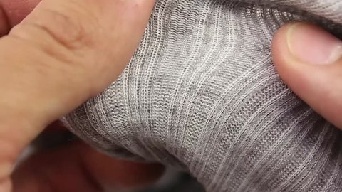 human hand testing gray wool thermal underwear, closeup(macro)