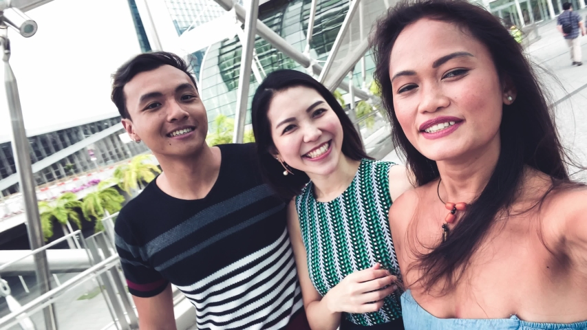 Three asian friends enjoying outdoor city life, taking selfies and making grimaces to the camera. Friendship and holiday concept. | Shutterstock HD Video #1045221178
