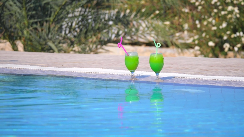 A young bald modern caucasian man with a mustache and beard in sunglasses swims in pool, swims to side and drinks a beautiful bright green cocktail through a straw. Summer vacation in the pool. | Shutterstock HD Video #1045226668