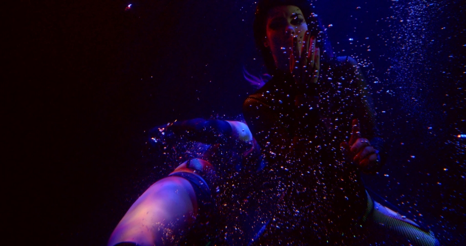 Two Sexy Girls with long hair are swimming in the Studio under water on a blue-red background in a pile of bubbles. They wear short tops and shorts. | Shutterstock HD Video #1045228348