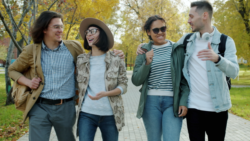 Happy friends tourists in casual clothes are walking in city park with backpacks talking and laughing on autumn day. Friendship, young people and tourism concept. | Shutterstock HD Video #1045402108