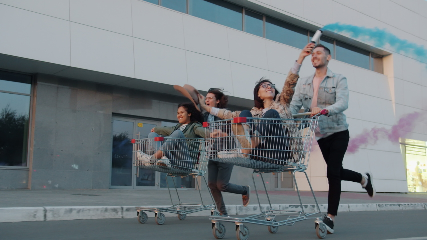 Cheerful youth men and women are riding shopping carts in city street holding smoke flares laughing enjoying leisure time. Freedom and friendship concept. | Shutterstock HD Video #1045402138