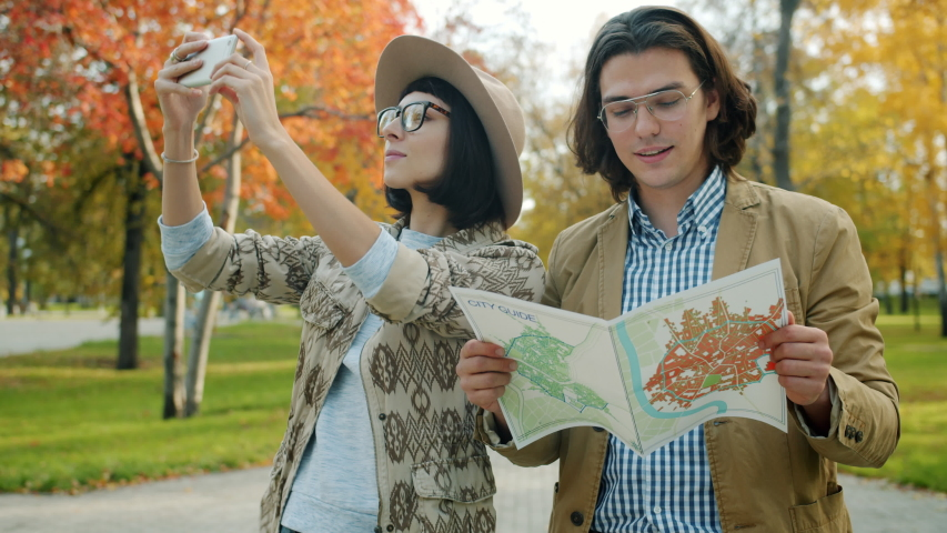 Joyful tourists man and woman looking at map and taking pictures with smartphone camera outdoors in city park then talking and laughing together. | Shutterstock HD Video #1045460968