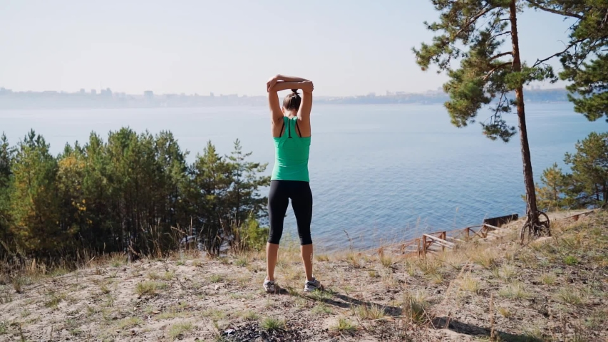 Girl runner doing muscle stretching on a high river bank. Warm up before jogging. | Shutterstock HD Video #1045937458