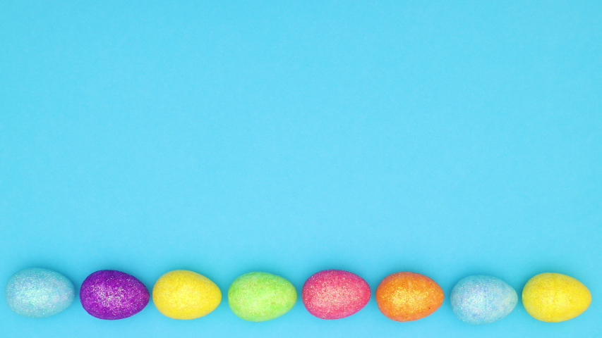 Easter eggs moving in circle on bottom of blue background - Looping stop motion  | Shutterstock HD Video #1046143858