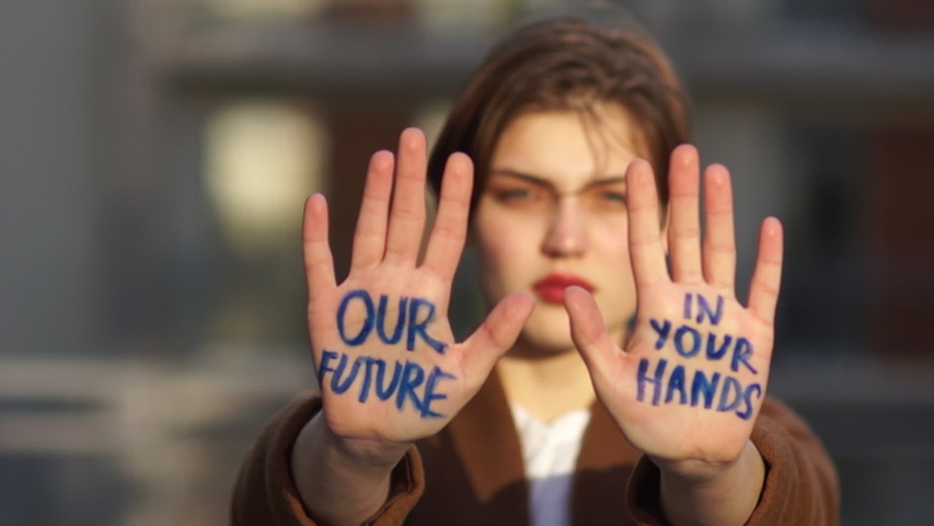 Climat strike, environmental disaster. Close portrait of a beautiful student with an inscription on the palms. Our future in your hands. Young woman protests against global warming | Shutterstock HD Video #1046280088