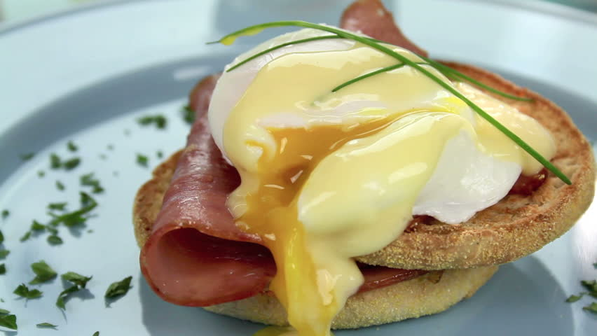 Oozing egg and ham benedict garnished with chives and parsley