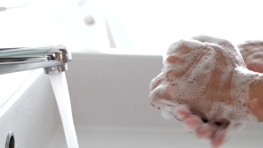 Hand of beauty woman  wash your hands at the wash basin with foam, cleanse the skin and have water flowing through the hands. Health and beauty concepts | Shutterstock HD Video #1046443618