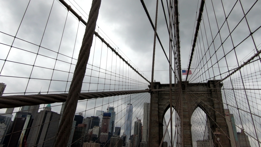 Walking on Brooklyn Bridge with Manhattan skyline in the background on a grey and cloudy day | Shutterstock HD Video #1046597488