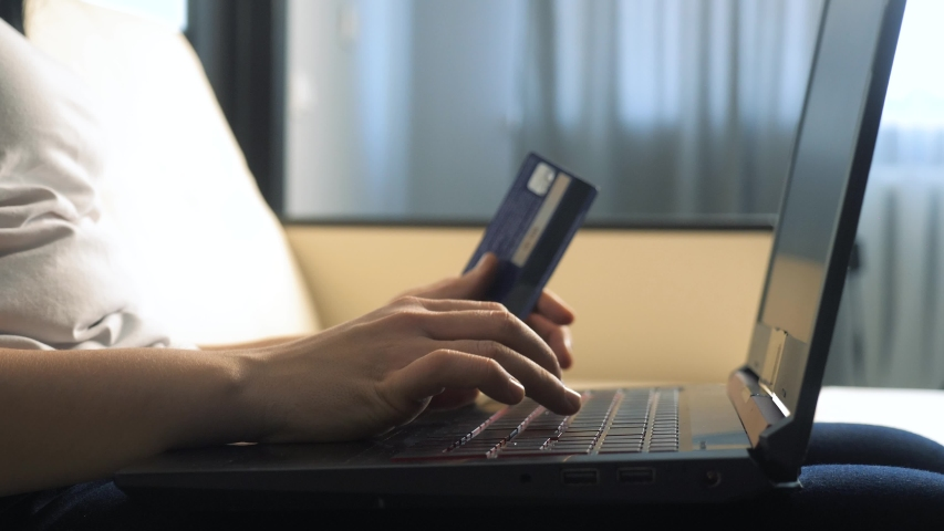 Girl makes online sale shopping concept with laptop digital tablet. brunette lying on the couch watching shop online paying credit card. Shop lifestyle online score | Shutterstock HD Video #1046814898