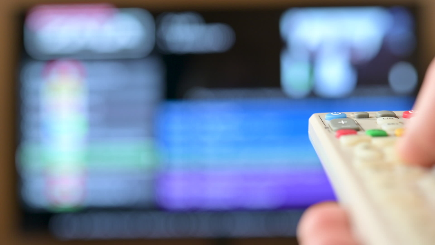 Watch TV. Closeup male hand switches television channels, on the background of the television screen. Program selection. | Shutterstock HD Video #1046822188