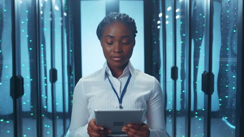 Black IT woman administrator providing digital analysis of server cabinet racks running app on notepad working at datacenter storage.   Shutterstock HD Video #1046828278