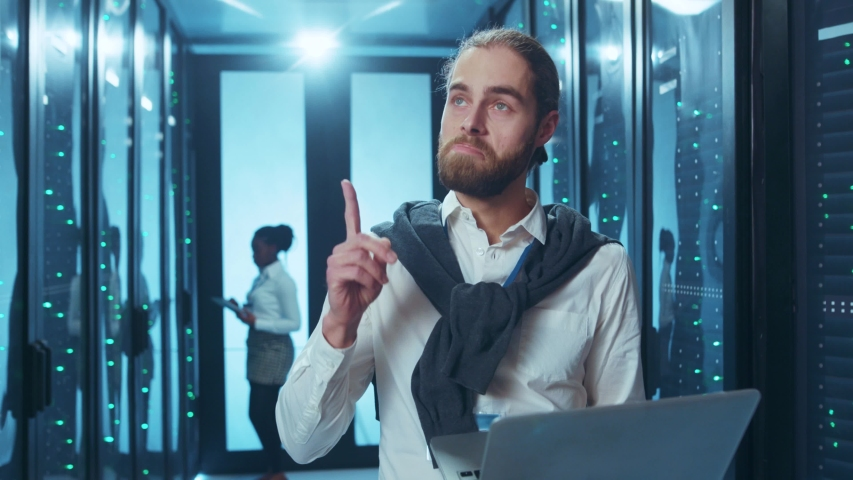 Inspired data center engineer holding a portable laptop and coming up with great success idea while collaborating with other colleague.   Shutterstock HD Video #1046828458