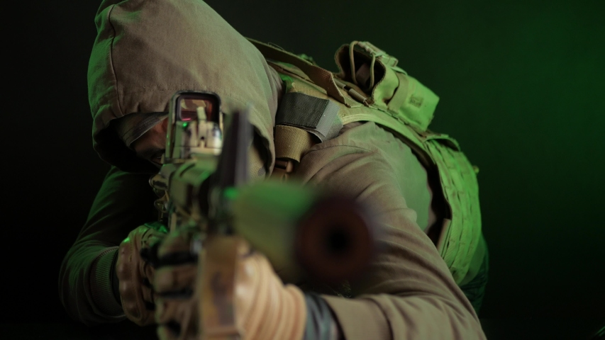 Military intelligence officer-spy, rebel takes aim at an automatic rifle | Shutterstock HD Video #1046882458