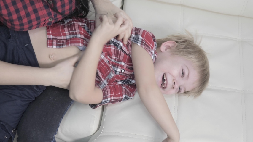 Happy family little boy laughs lifestyle from tickling mother. woman playing with son a happy family laughing indoors | Shutterstock HD Video #1046890858