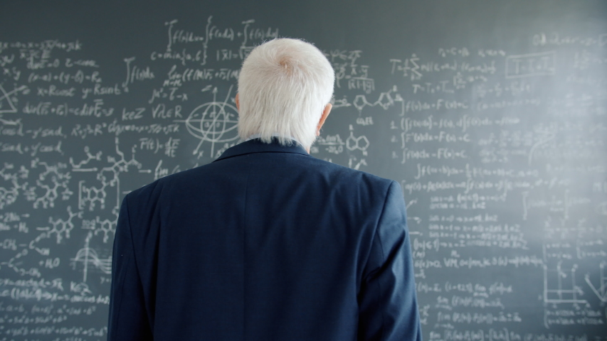 Mature man in suit is walking to chalkboard wall with formulas looking at equations holding chalk thinking about science. People, research and education concept. | Shutterstock HD Video #1046909218