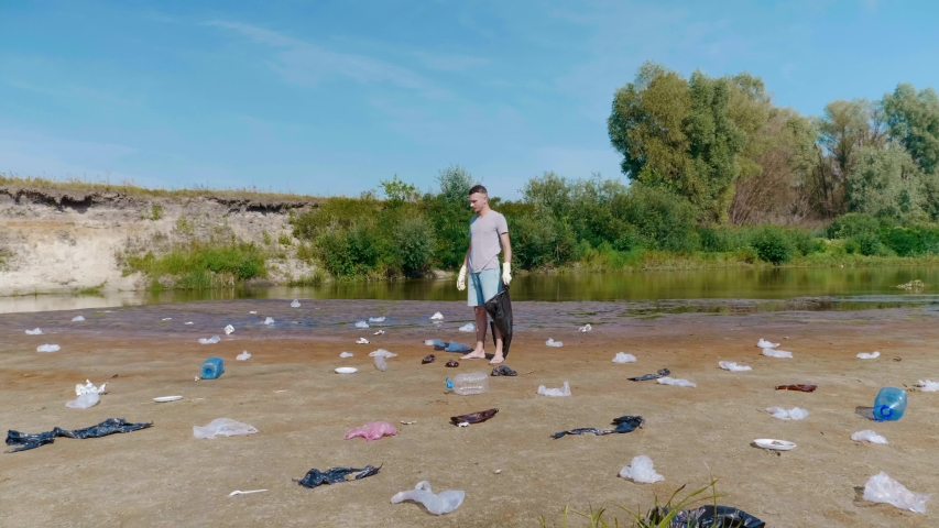 A man in a gray t-shirt and blue denim shorts is collects plastic trash on the banks of a dry and polluted river or lake. Ecological catastrophy. Anthropogenic influence. 4K slowmotion footage. | Shutterstock HD Video #1046929138