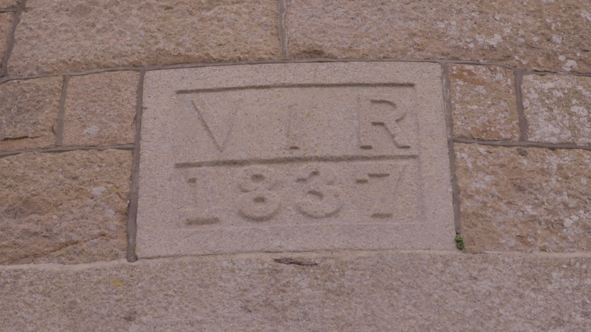 Close up of stone inscription VIR, 1837 above doorway at Victoria Tower in Jersey | Shutterstock HD Video #1046929978