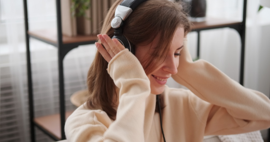 Woman listening to music on headphones | Shutterstock HD Video #1046970598