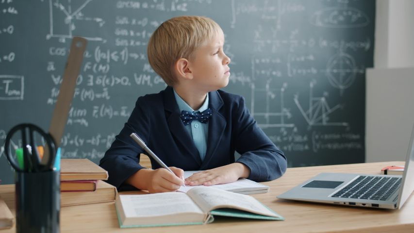 Prodigy kid in suit is taking notes sitting at desk in university classroom with chalkboard covered with formulas in background. Modern education and talanted children concept. | Shutterstock HD Video #1046977108