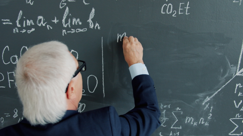 Back view of smart senior man university professor writing equations on chalkboard in class focused on scientific calculations. People and education concept. | Shutterstock HD Video #1046982808