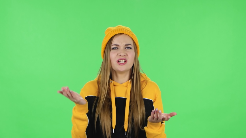Portrait of modern girl in yellow hat is reporting and telling a lot of interesting information. Green screen | Shutterstock HD Video #1047020248