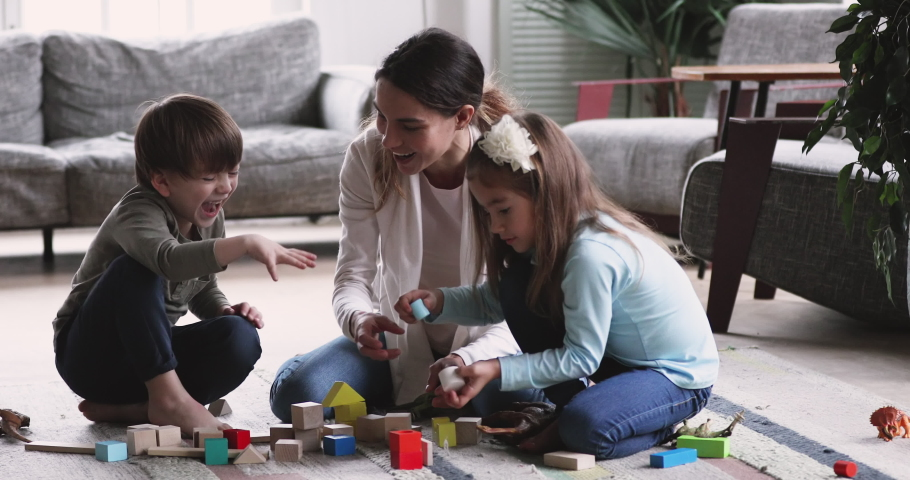Happy young adult mother nanny playing with two cute small kids, having fun sit on floor carpet at home. Playful mum helping preschool children building tower of wooden blocks in living room | Shutterstock HD Video #1047050968