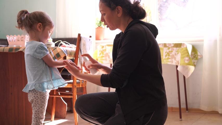 Coronavirus mers. Mom treats daughter's hands with disinfectant spray. Disinfection Efforts Against Coronavirus. Travel hand sanitizer | Shutterstock HD Video #1048484458