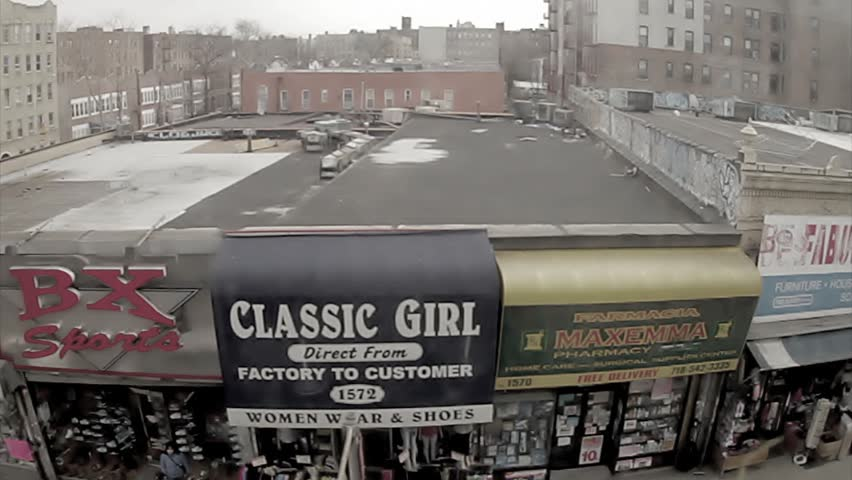 NEW YORK - FEB 9, 2010: classic South Bronx stores and streets, elevated subway train view of ghetto in 70s style vintage 16mm footage, NY. Bronx is the northernmost borough in NYC.