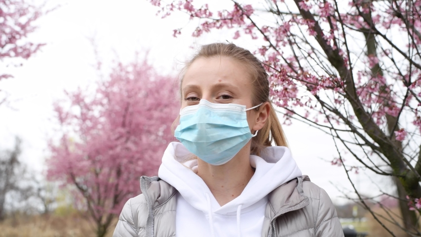 Beautiful woman takes off a medical mask and enjoying blooming tree after allergy | Shutterstock HD Video #1049375008