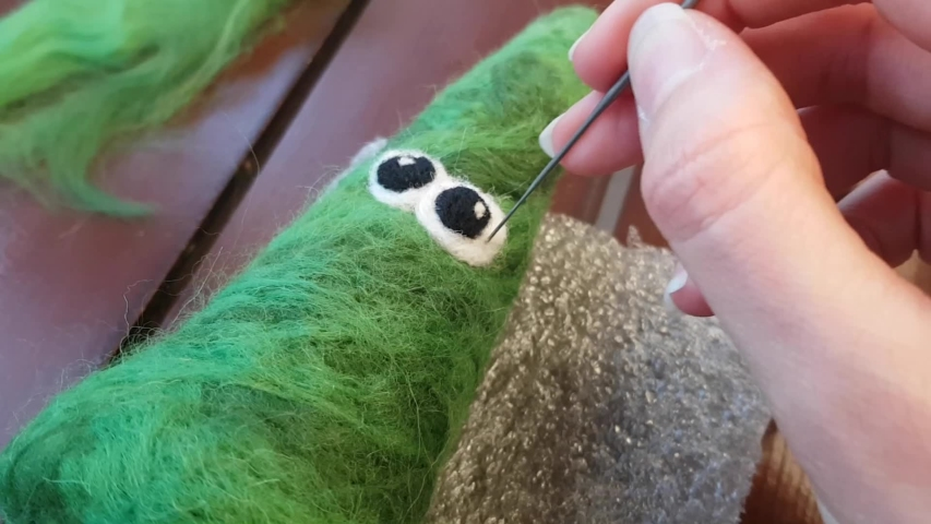Dry felting. Needlework. Work with a needle on the wool on the table. Toy in the form of a funny Christmas tree. Semiproduct. | Shutterstock HD Video #1049503288