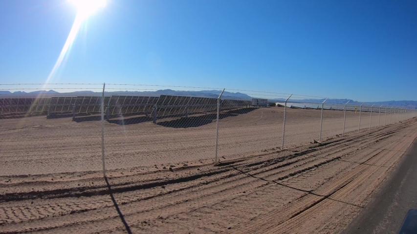 POV driving past solar energy farm with chain fence in desert - Nevada | Shutterstock HD Video #1049511808