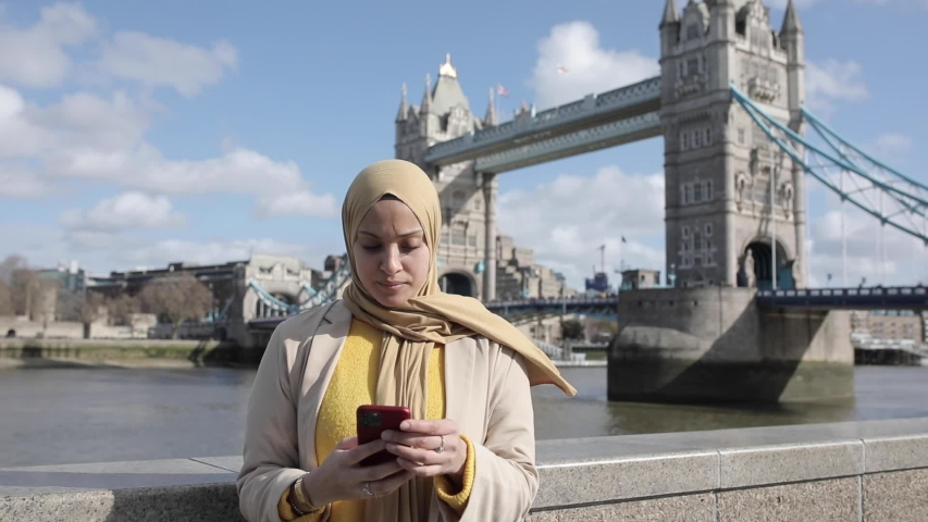 Smiling woman wearing hijab and taking a selfie at London Bridge | Shutterstock HD Video #1049571508