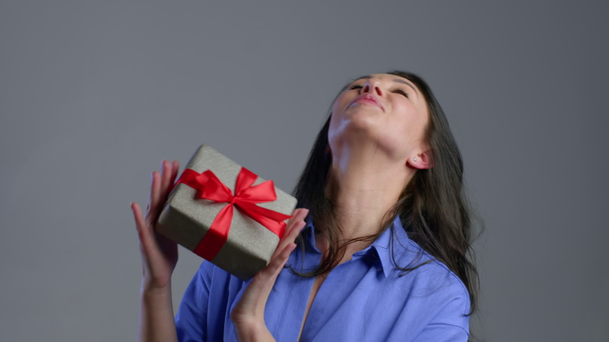 Excited adult woman received gift box with bow. She is happy and flattered by attention. Mature lady dancing with present on grey background. Studio footage. 4k. | Shutterstock HD Video #1049615758