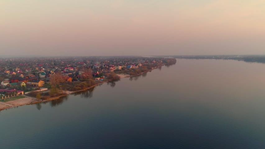 Golden sunset over suburbia near river or lake. Aerial drone shot. Water and late evening. | Shutterstock HD Video #1049665738