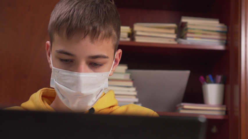 Distance learning of a teenager with a laptop at home while quarantining from coronavirus. In a protective face mask in a room with a closet with school supplies | Shutterstock HD Video #1049712298