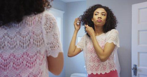 Beautiful black woman fixing hair in the morning
