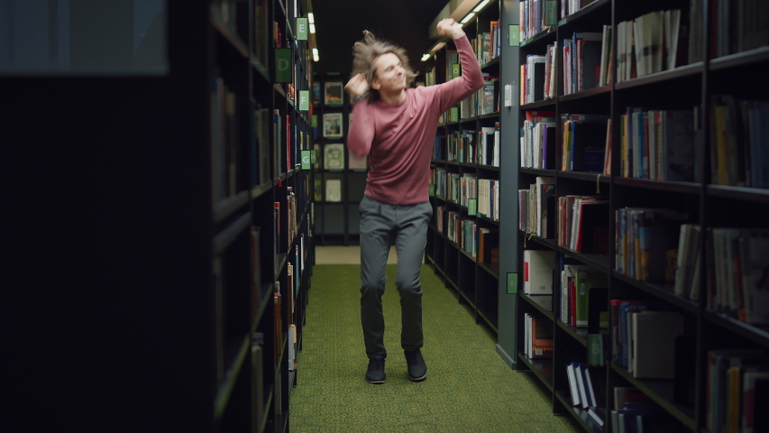 University Library: Handsome Caucasian Student Celebrates Successful Pass of Exams, Dances Between Rows of Bookshelves. Success in College: Admission, Graduations, Finishing Master Thesis | Shutterstock HD Video #1049866978