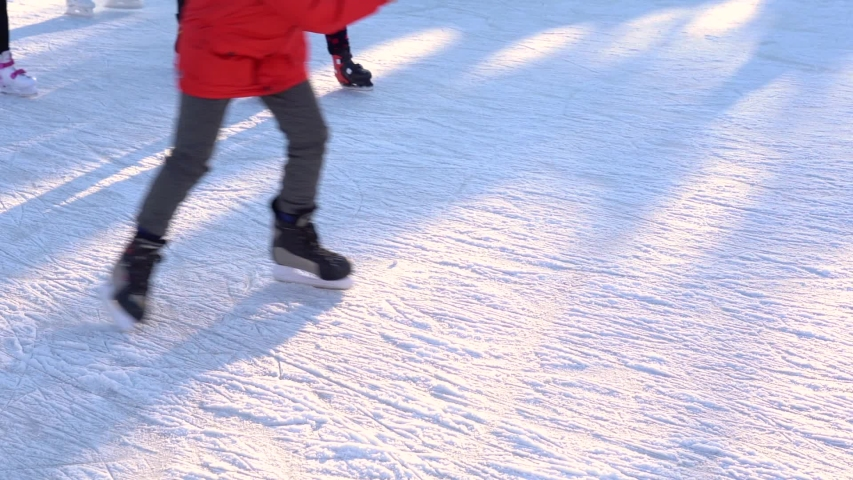 Group of people of different ages having fun outdoor in winter on ice rink. Many people skating cheerfully. | Shutterstock HD Video #1049932048