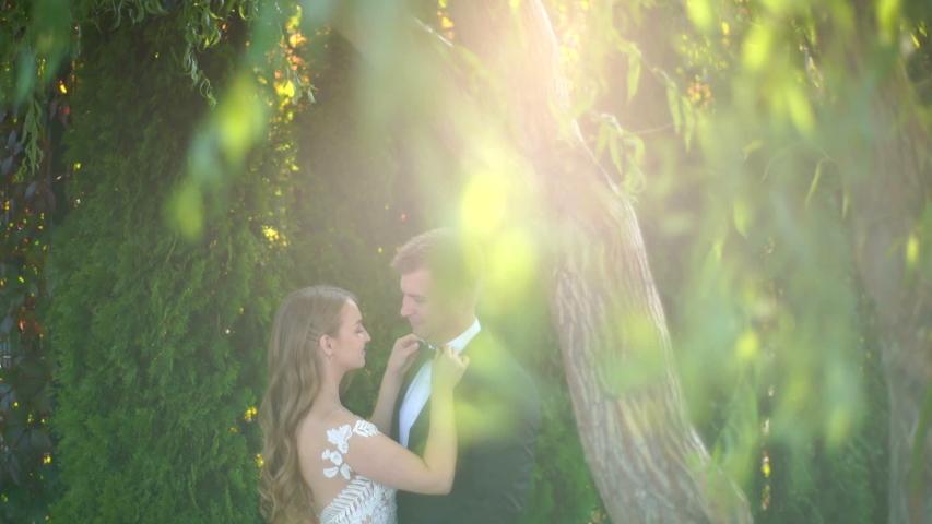 Wedding couple walking in the park. Wedding couple walking with beautiful park. Young couple in love. Slow motion | Shutterstock HD Video #1050010168