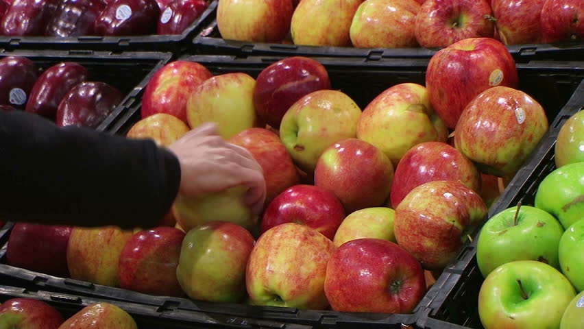 Woman selecting fresh red apples in grocery store produce department. | Shutterstock HD Video #1051648