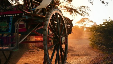 Slow motion video of traditional wooden horse cart moving by rural country road of Bagan Buddhist historical site. Bright sunshine and sun rays of summer sunset