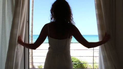 Beautiful girl open white curtains and go to sea view terrace, wind move her hair. Adult wakind up woman looking at blue sky, ocean beach landscape horizon from balcony in summer vacation. HD video