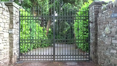 Ornate iron gates opening and closing with leafy driveway in the background