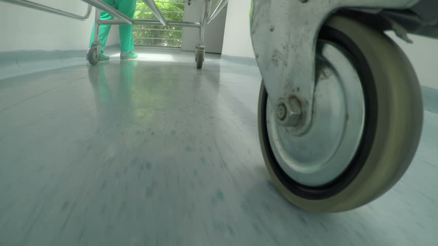 Low level close up of medical professional bed wheel moving on hallway