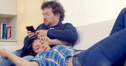 Man cheating on wife with cell phone while she is sleeping
