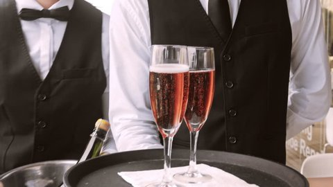 4k medium steadicam video of waiter and champagne glasses on a tray, walking to a customer in hotel or restaurant.