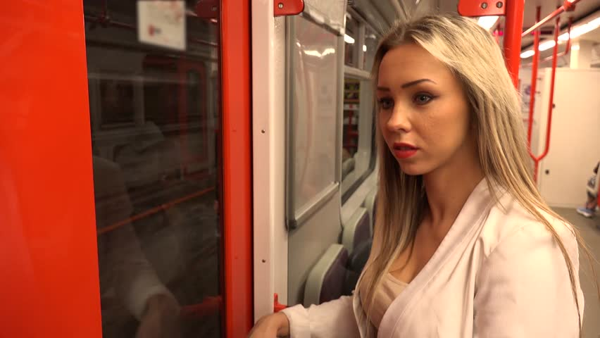 Young attractive blonde woman traveling by subway and looks around - other people in the background  | Shutterstock HD Video #10644896