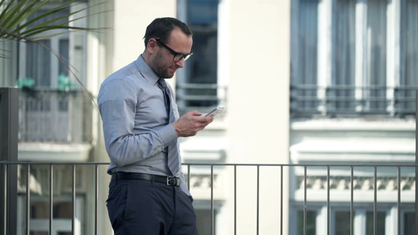 Young businessman using smartphone standing on balcony 