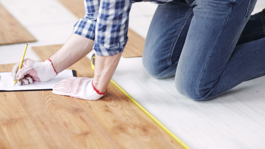 Repair, building, floor and people concept - close up of man measuring flooring with ruler and writing to clipboard | Shutterstock HD Video #10692728